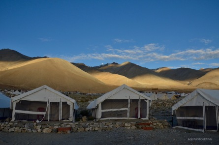 Early morning view of the tents and moon setting behind the mountains